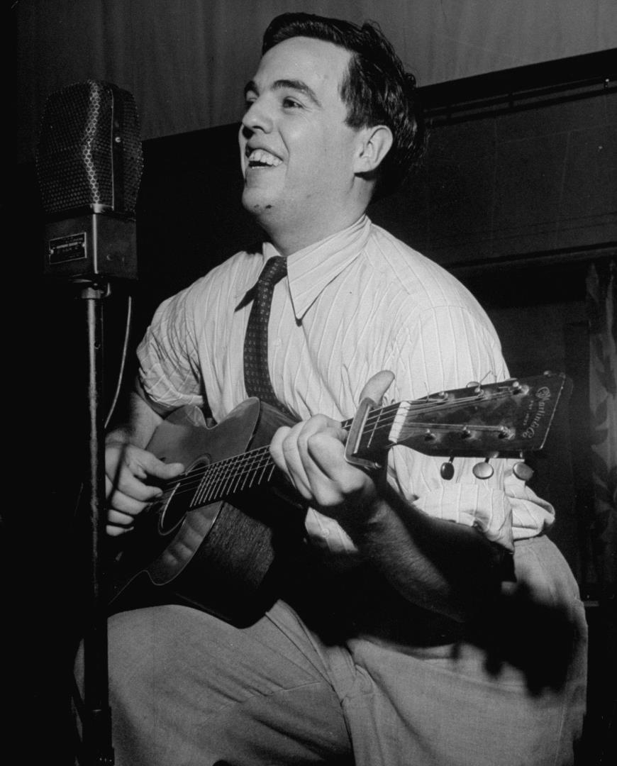 Alan Lomax playing guitar and singing in Washington, DC in July 1946.