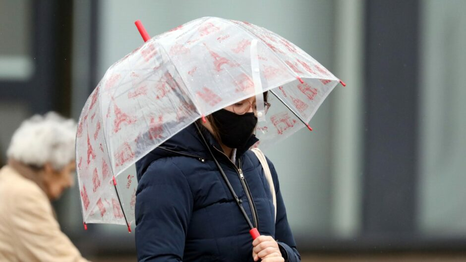 A person walking under an umbrella in Dundee city centre during heavy rain.