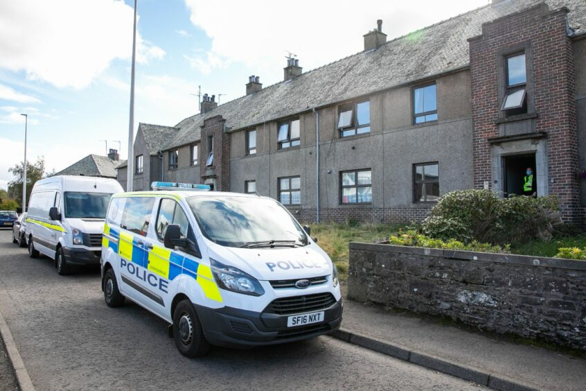 A police van and fire van parked outside a block of flats in Forfar following a fatal fire.