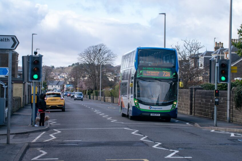 A double-decker Stagecoach bus driving past a pedestrian crossing on a road in Monifieth.