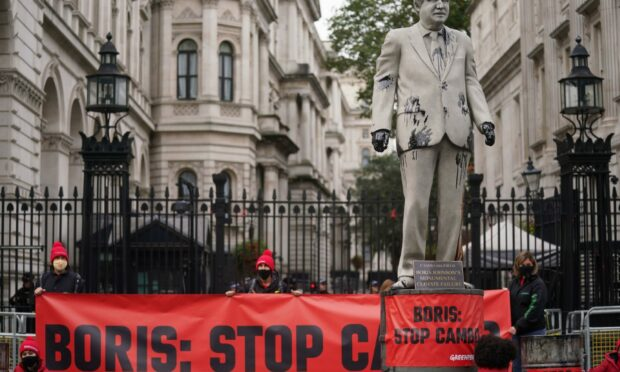 A statue of Prime Minister Boris Johnson splattered with oil as campaigners from Greenpeace demonstrate Downing Street, London, against the Cambo oil field off the west coast of Shetland.