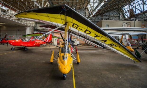 A yellow flexwing microlight in the Scottish Aero Club hangar.
