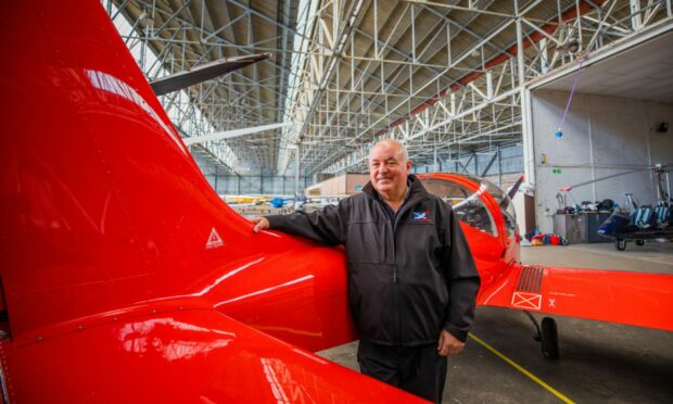 Kevin Whitehead from Alba Airsports standing next to a red fixed wing microlight.