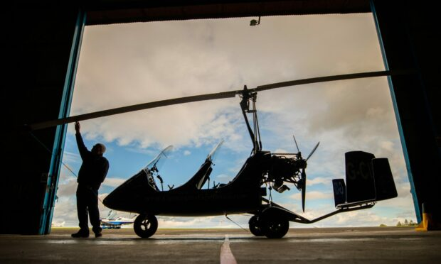 A silhouette of Kevin Whitehead from Alba Airsports checking the rotor blades of his gyrocopter.