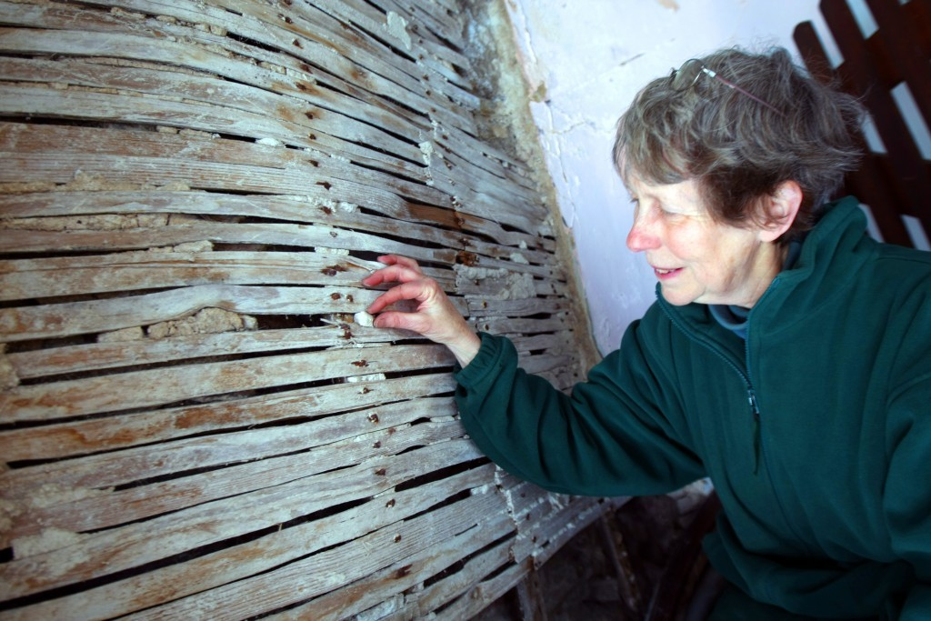 Archivist Jane Anderson looks at wooden banding is used to support plaster work.