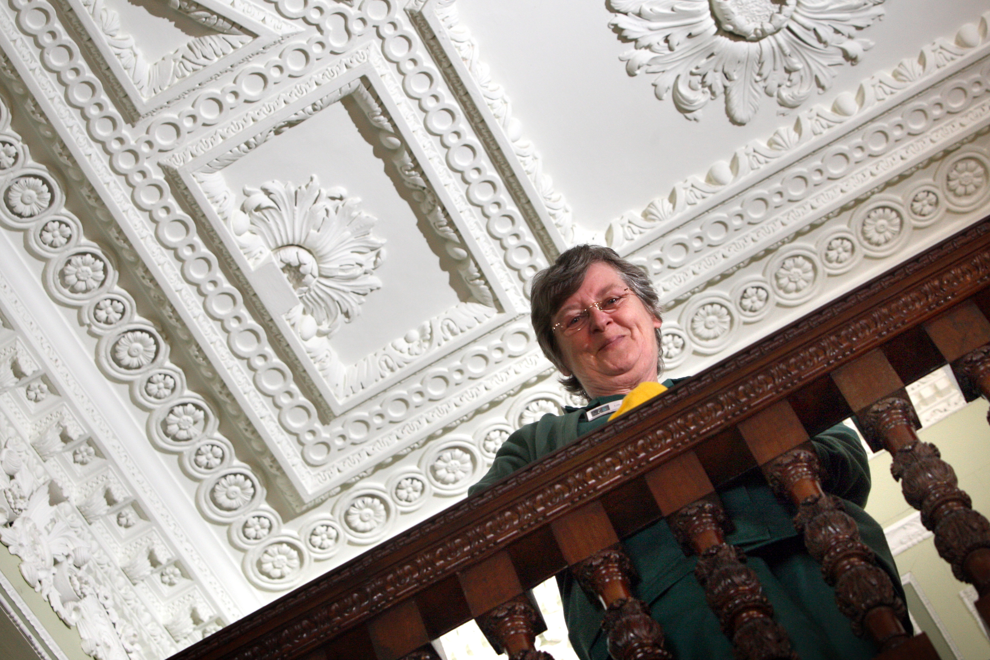 Lillian Lamond from the house keeping team with the Syrian-inspired front stair ceiling cornice and plaster work behind her.