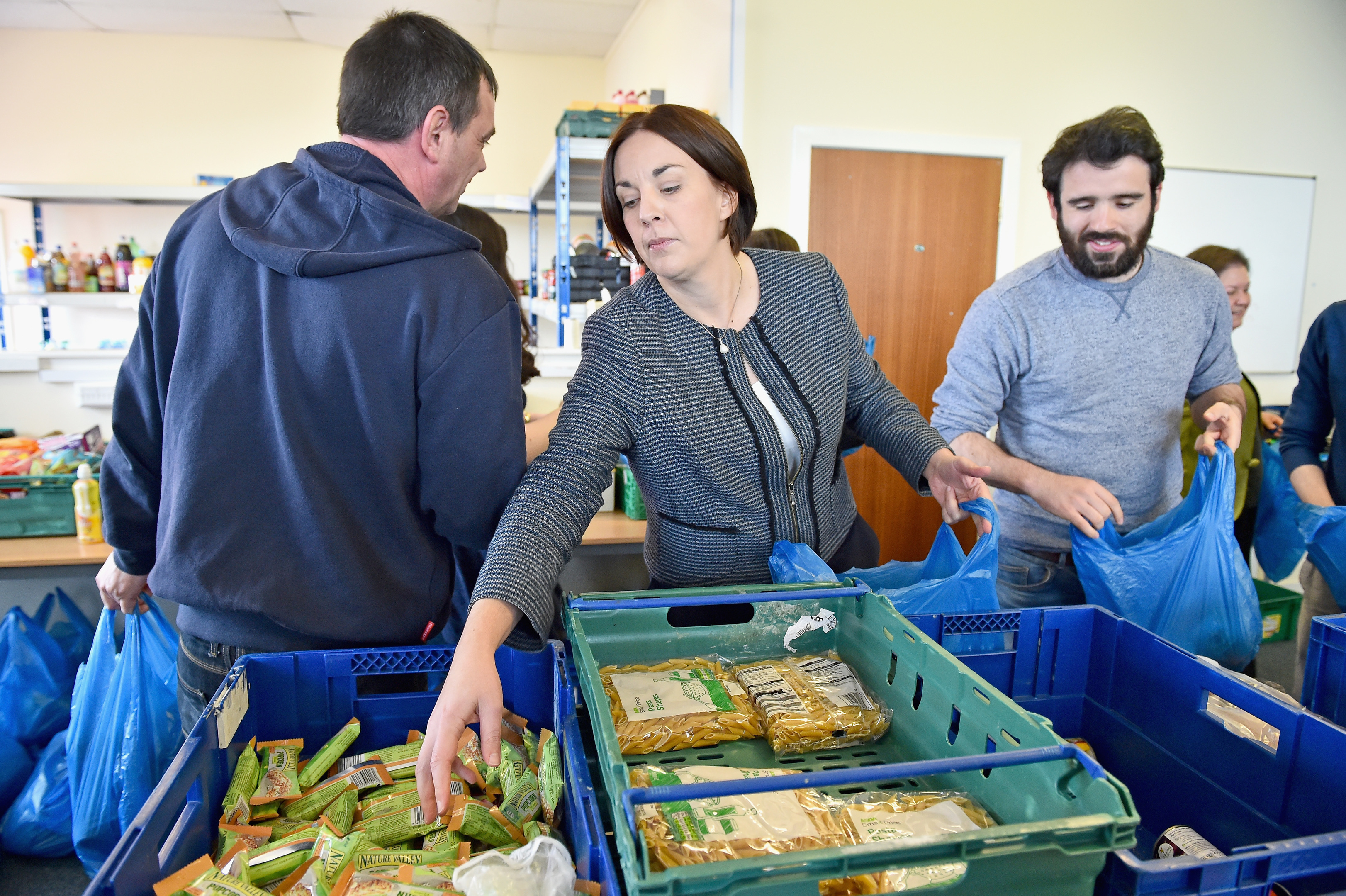 Kezia Dugdale helps staff and volunteers pack food bags for distribution at a community food share  in Dumbarton.