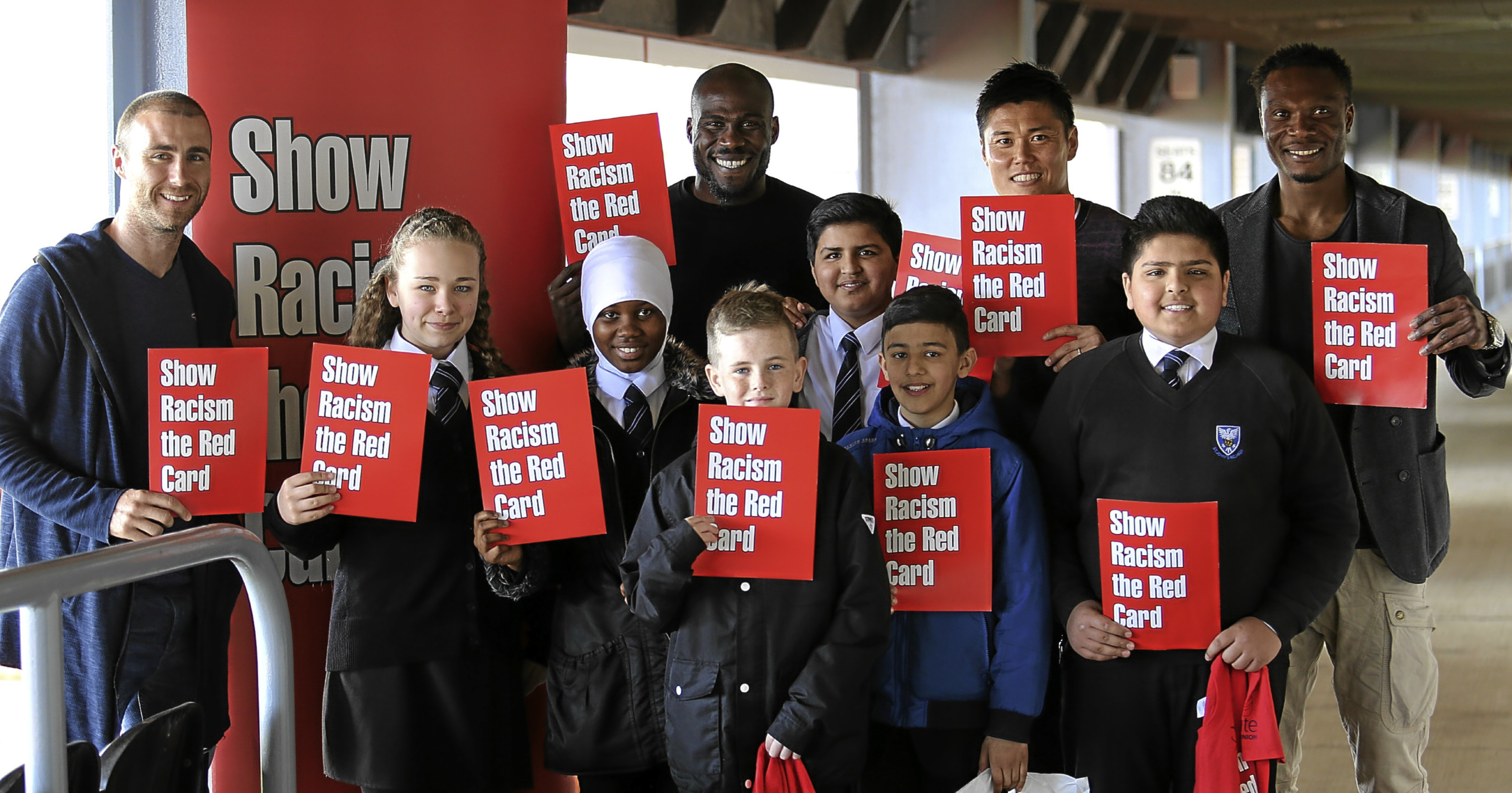 """Children and Dundee United FC unite to """"show racism the red card"""" at an event in 2016."""