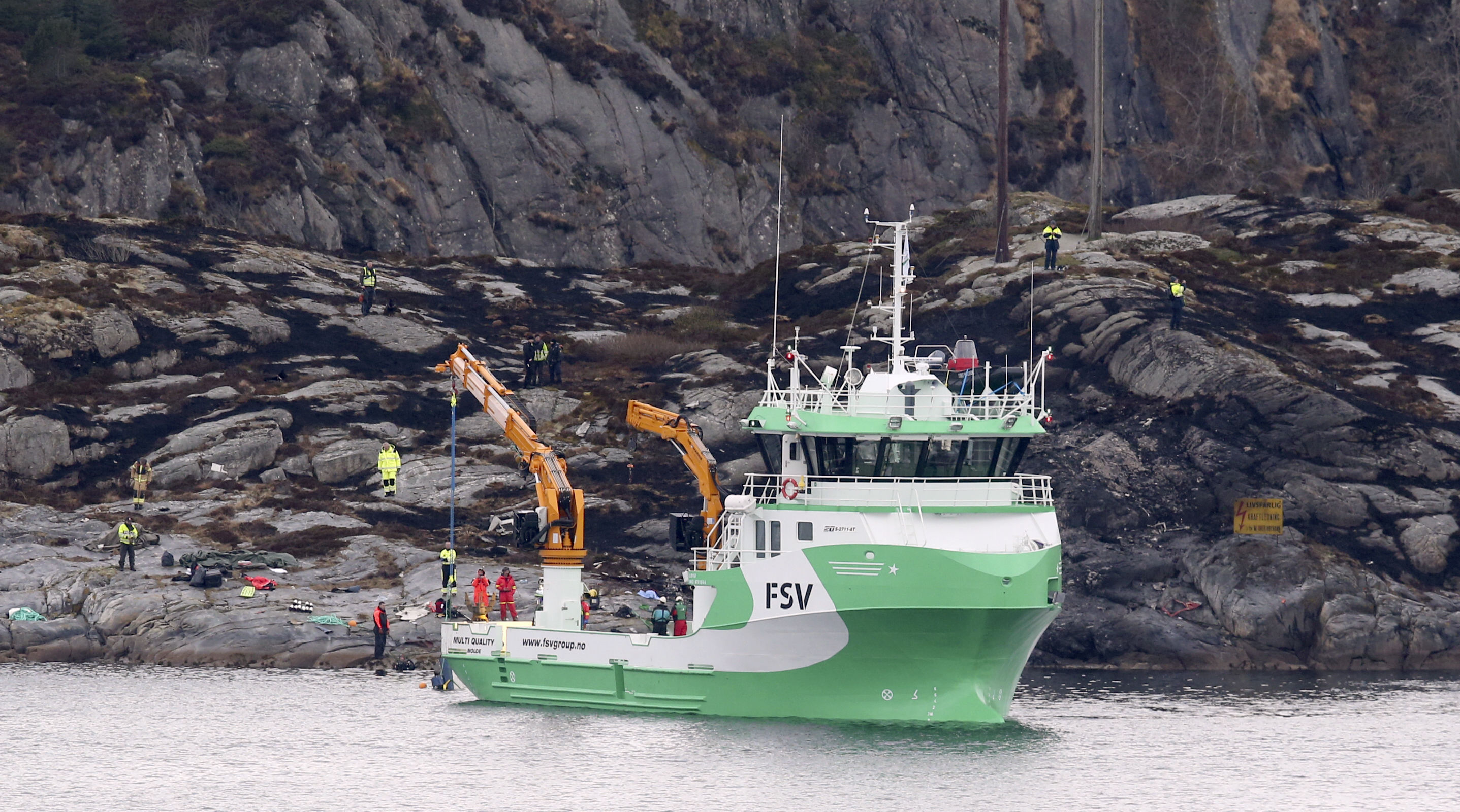 A recovery vessel lifts up parts of the crashed helicopter from off the island of Turoey, near Bergen, Norway.