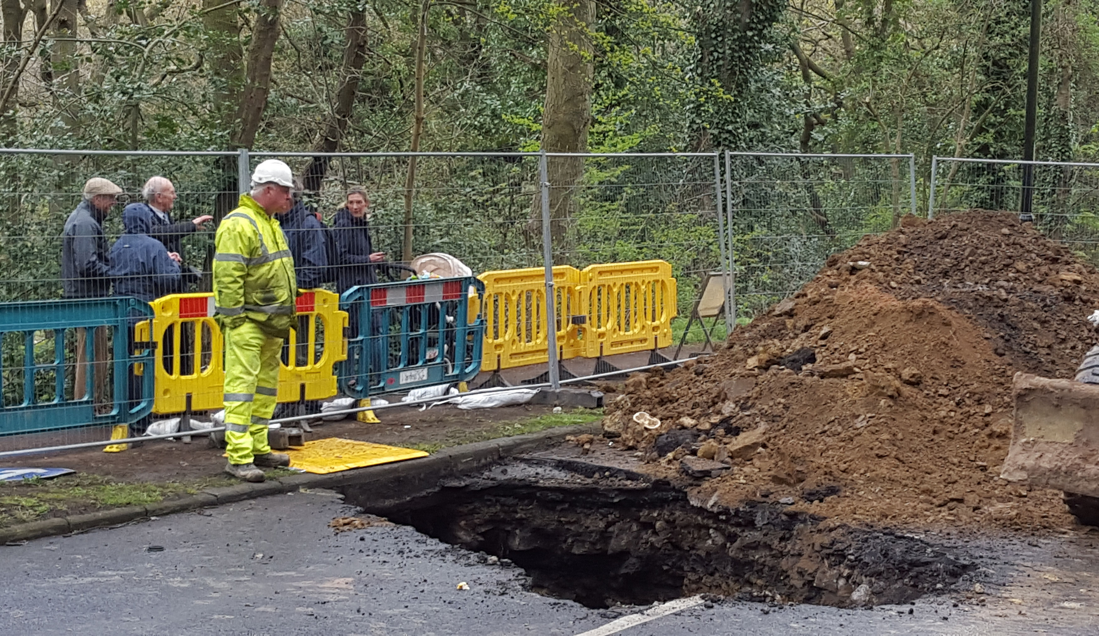 Members of the public look on as work is carried out on a sinkhole more than 20ft deep in Sheffield.