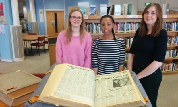 Students Mhairi Anderson, Nesha Dixon an Amy Morrison trawl through an old newspaper for clues.