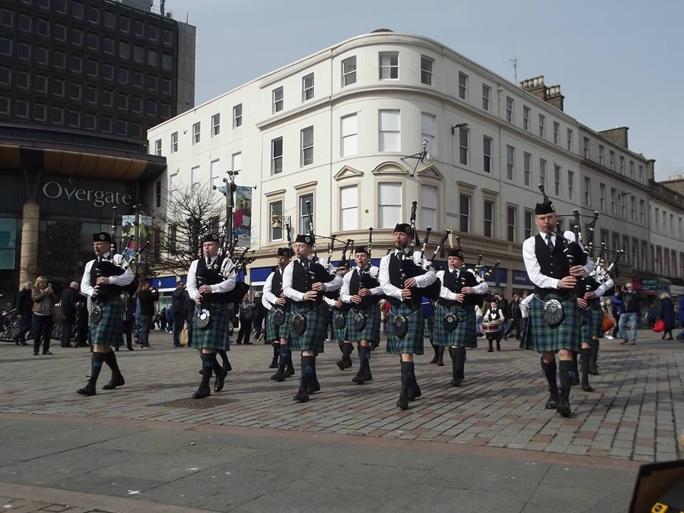 The Mackenzie Caledonian Pipe Band performing outside the Overgate