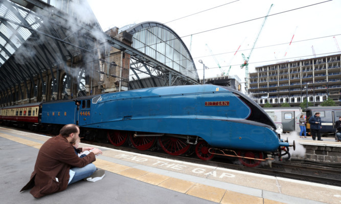 The Bittern steam train which is sister train to the Mallard leaves King Cross in Central London.