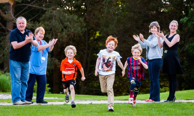 Back, from left: John Walker, TCCL lodge treasurer, Gaye Steel, paediatric oncology nurse specialist, Morag Senyszak, TCCL committee member, and fundraiser Hazel Taylor. Centre, from left: Hazels children Omri, 5, Jude, 10, and Gene, 8, with the boys showing that the athletic skills run in the family.