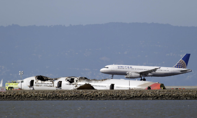 A United Airlines plane lands next to the  wreckage of Asiana Flight 214 at the San Francisco International Airport on Sunday.