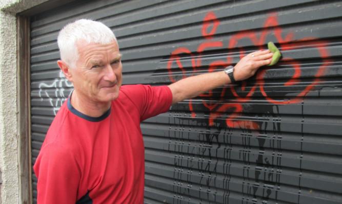 Martin Squibbs washing paint off a garage door at Blackness Road.