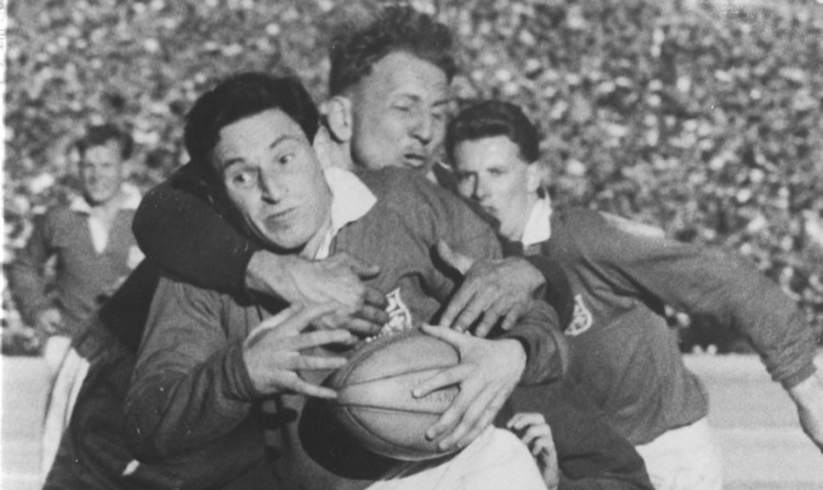 Welsh rugby union fly-half Cliff Morgan is tackled while playing for the British Lions against South Africa at Johannesburg in August 1955.
