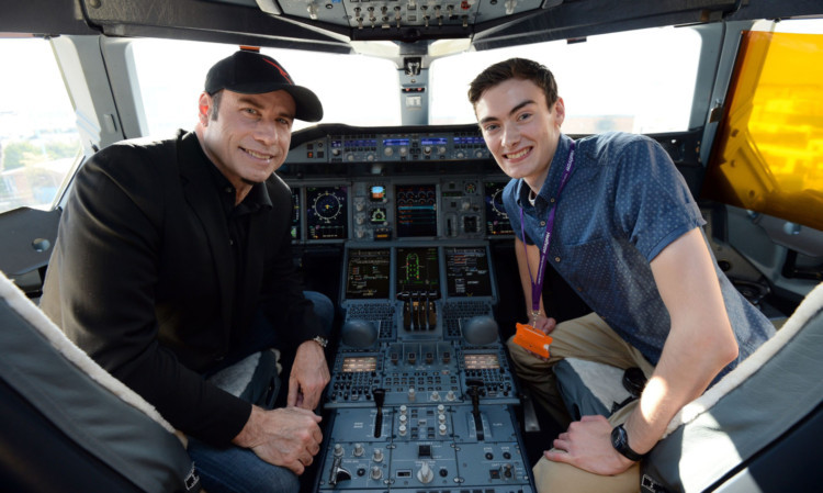 Tom Hall and John Travolta in the cockpit and, below, with Qantas flight staff.