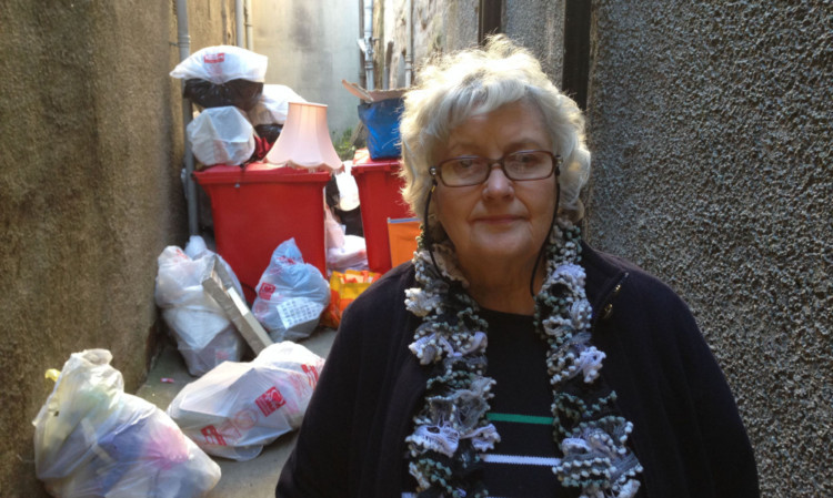 Moira Dewhurst beside rubbish dumped at the back door of the British Heart Foundation charity shop in Perths High Street.