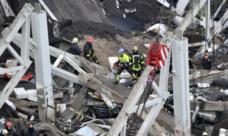 Rescue workers searching debris for survivors.