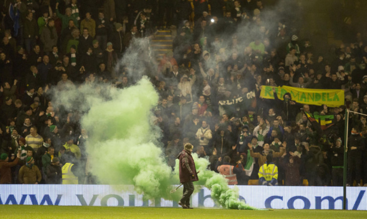 Celtic fans throw flares on to the pitch before a recent Premiership match at Fir Park, Motherwell. The initial ban on flags and banners at McDiarmid Park came about over fears they would be used to conceal flares.