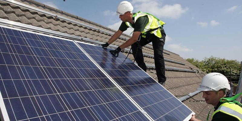 File photo dated 27/04/2011 of workmen installing solar panels on to the roofs of homes in Delabole near Bodmin.