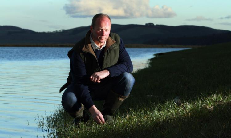 David Hay beside the flooded farmland.