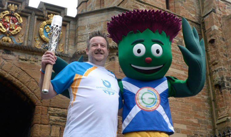 Baton bearer Graeme Lawson with Games mascot Clyde the Thistle at Linlithgow Palace.