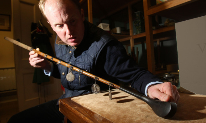 Auctioneer Nick Burns with a golf club that sold to a private collector for £2,700.