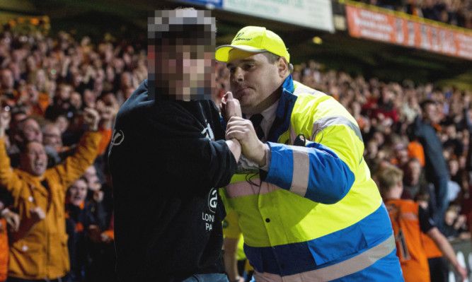 A fan is escorted off the pitch by a steward.