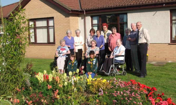 Residents and Scouts enjoy the new garden at Gillie Court.