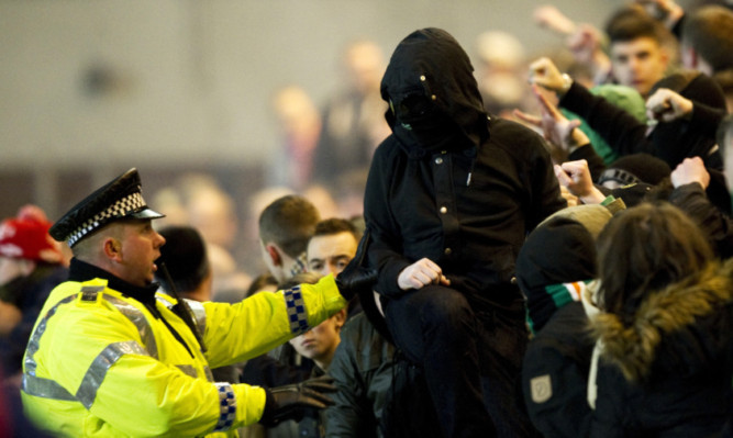 A policeman deals with Celtic supporters at Dens on Wednesday.
