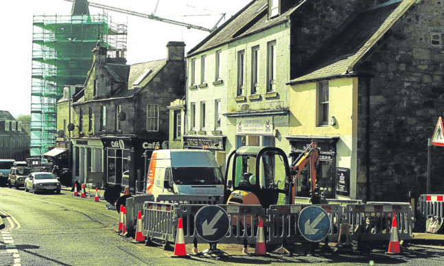 Roadworks on High Street, Kinross, with the town hall encased in scaffolding in the background.