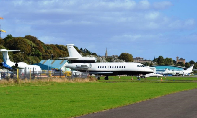 Private jets and helicopters at Dundee Airport.