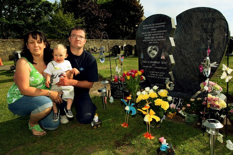 John Stevenson, Courier,03/06/10.Dundee.Barnhill Cemetery.Pic shows Alana and Mark Fraser with year old son Zak at the graveside of their twins Saul and Savanah-Rose.The council have asked the couple to remove all tributes from the graveside.