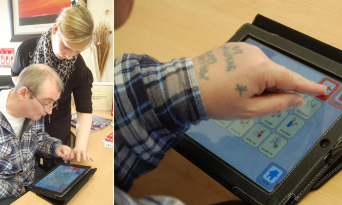 Kevin Beverley using his iPad with support worker Kerry Ramsden.