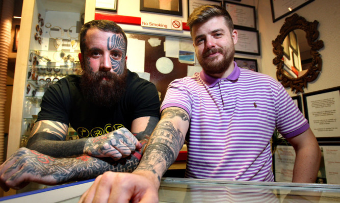 Tattoo artist Calum Stewart, left, with Jamie Shankland, who had a tattoo showing crowds of Dundonians gathered at the H Samuel clock inked on his arm.