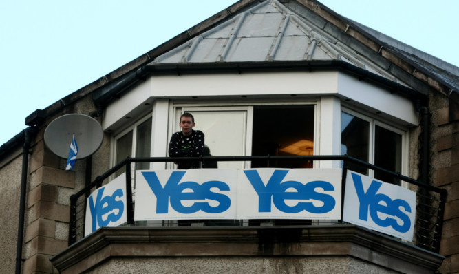 Jason Brown on the balcony of his flat on Caledonian Road in Perth, with his highly visible Yes banners. He will now take them down.