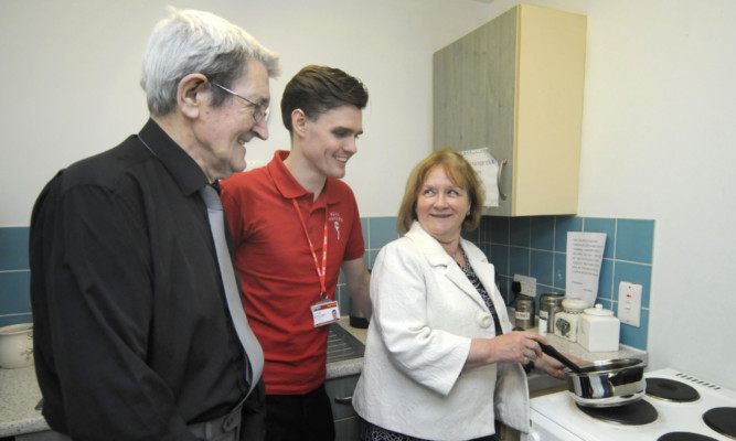 Minister for Public Health Maureen Watt visits Meal Makers and shows she can cook too, watched by Norman Quigg, left, the first recipient of the schemes help, and Meal Makers development officer Stuart Miller.