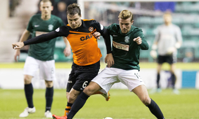 Dundee Utd's Paul Paton wrestles for the ball with Hibs' Danny Handling