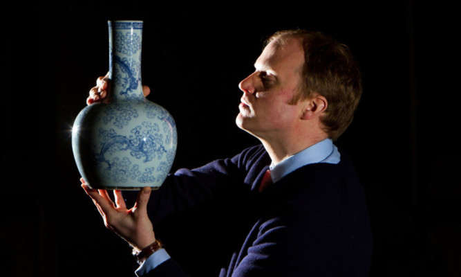 Auctioneer Nick Burns shows off the vase, which carries a Chenghua mark.