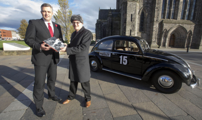 Mark Macmillan, leader of Renfrewshire Council, and Douglas Anderson with his book at Paisley Abbey