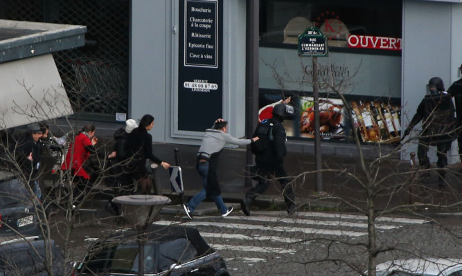 People are led away from the hostage scene at the supermarket in Paris.