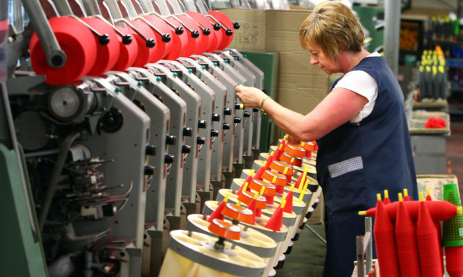 A worker involved in the cashmere yarn manufacturing process at Todd & Duncan of Kinross. Scotlands private-sector economy ended the year on a sound footing.