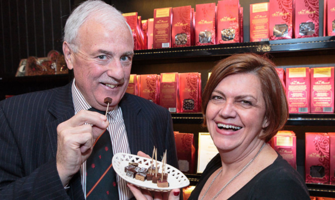 St Andrews Business Club president Kenneth Russell samples one of the chocolate truffles offered by Julie Collier of Iain Burnett the Highland Chocolatier at the shop on South Street, St Andrews.