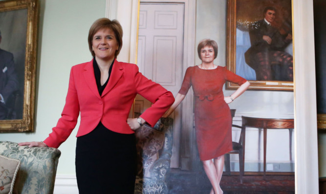 First Minister Nicola Sturgeon stands next to her life size portrait.