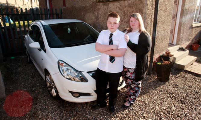 Gillian Garty and her son Logan beside their vandalised car on Balmuir Road.
