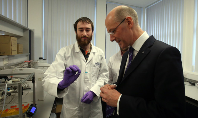 Deputy First Minister John Swinney views a 3D structure made by the 3D Bio Printer, held by Dr Alan Faulkner-Jones, during a visit to the Heriot-Watt Life Sciences Laboratory.