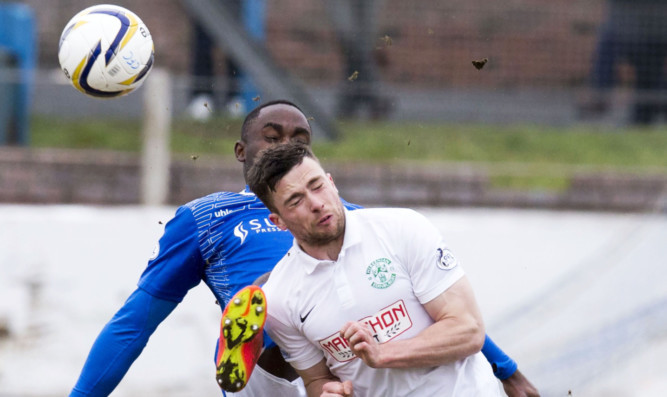 Kudus Oyenuga battles Hibs Lewis Stevenson for the ball.