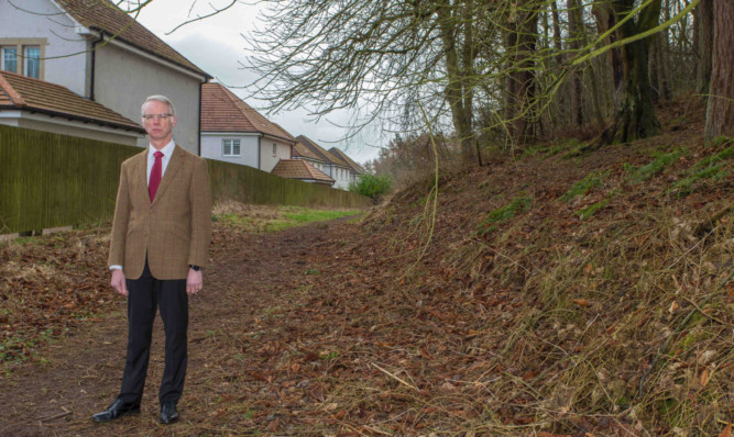 Mr Wincott in one of the woodland areas residents say needs more attention.